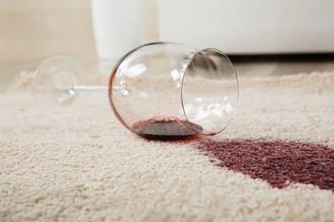 A glass of red wine spilt on a carpet